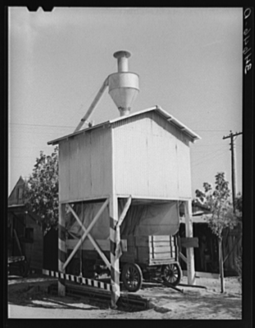 Wagon on scales at feed mill. Taylor, Texas. Ground feed is poured directly into the wagon from the hopper above