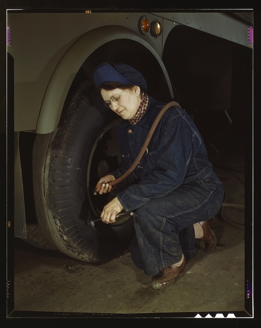 War production workers at the Heil Company making gasoline trailer tanks for the U.S. Army Air Corps., Milwaukee, Wisconsin. Mrs. Angeline Kwint, age 45, an ex-housewife, checking the tires of trailers. Her husband and son are in the U.S. Army