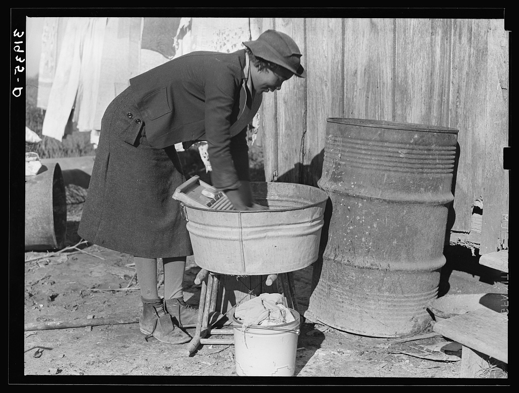 Washing clothes at rear of sharecropper's cabin. Transylvania, Louisiana