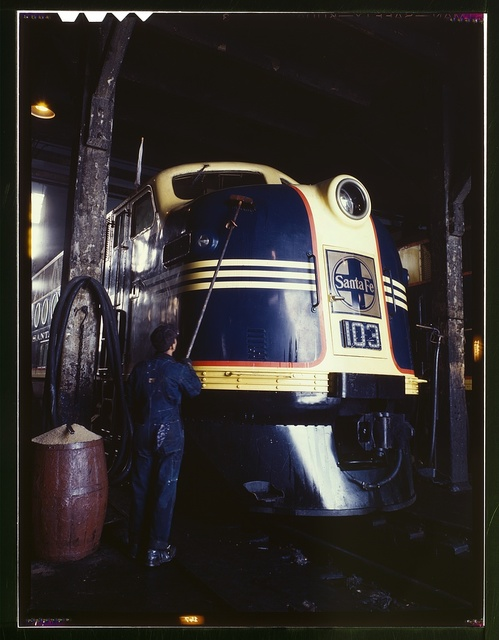 Washing one of the Santa Fe R.R. 54 hundred horse power diesel freight locomotives in the roundhouse, Argentine, Kansas. Argentine yard is at Kansas City, Kansas