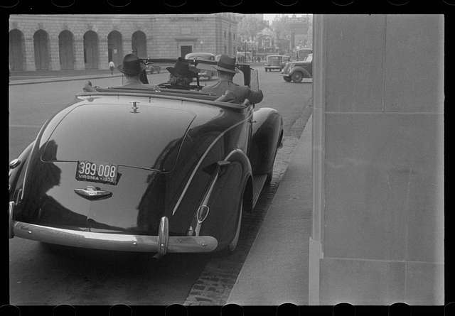 Washington, D.C. A street scene, showing a car at the entrance of the Office of Internal Revenue, facing the Benjamin Franklin post office qt 12th and Pennsylvania Avenue