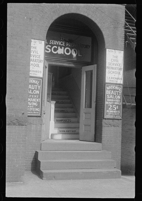 Washington, D.C. Entrance to an old building at 529-12th Street, with signs beside the door advertising the Civil Service Preparatory School and the National Beauty Salon