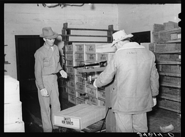 Weighing box of turkeys to be loaded into freight car at cold storage plant. Brownwood, Texas. Sheepskin coat is necessary because of low temperature in cold storage plant