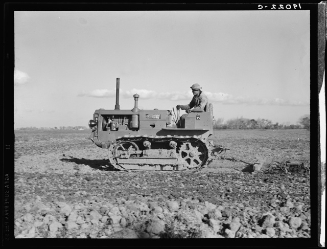 West side of San Joaquin Valley, California. Caterpillar diesel type tractor is common in California. Only very large-scale operations can afford this type. Cultivating potato-fields