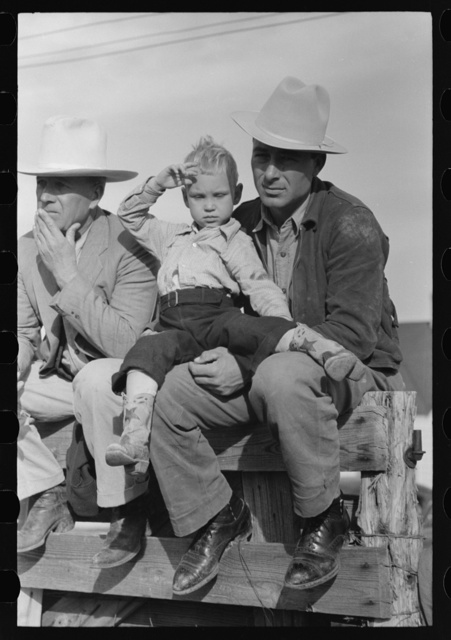 West Texan and his son sitting on fence at horse auction, Eldorado, Texas