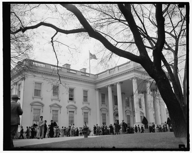 White House mecca for Easter holiday sightseers. Washington, D.C., April 11. Easter Holidays bring thousands of visitors to the Capitol every year. Naturally, the first stop for the sightseers is the White House as this picture indicates. 4-11-39