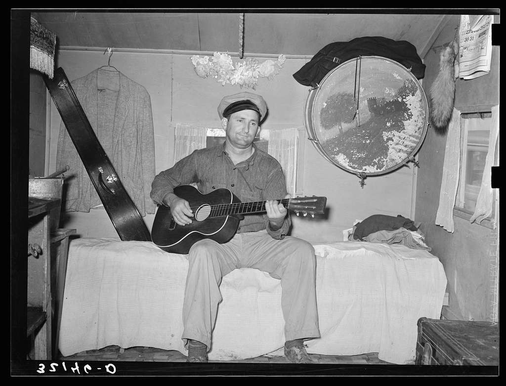 White migrant playing guitar in trailer home. Weslaco, Texas