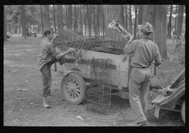 White migrant strawberry picker unloading automobile cushion springs from trailer. These will be used as bed springs. Hammond, Louisiana