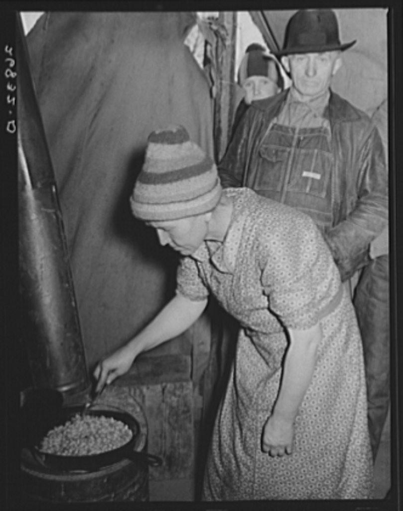 Wife of evicted sharecropper in tent along highway cooking beans obtained from surplus commodities. New Madrid County, Missouri