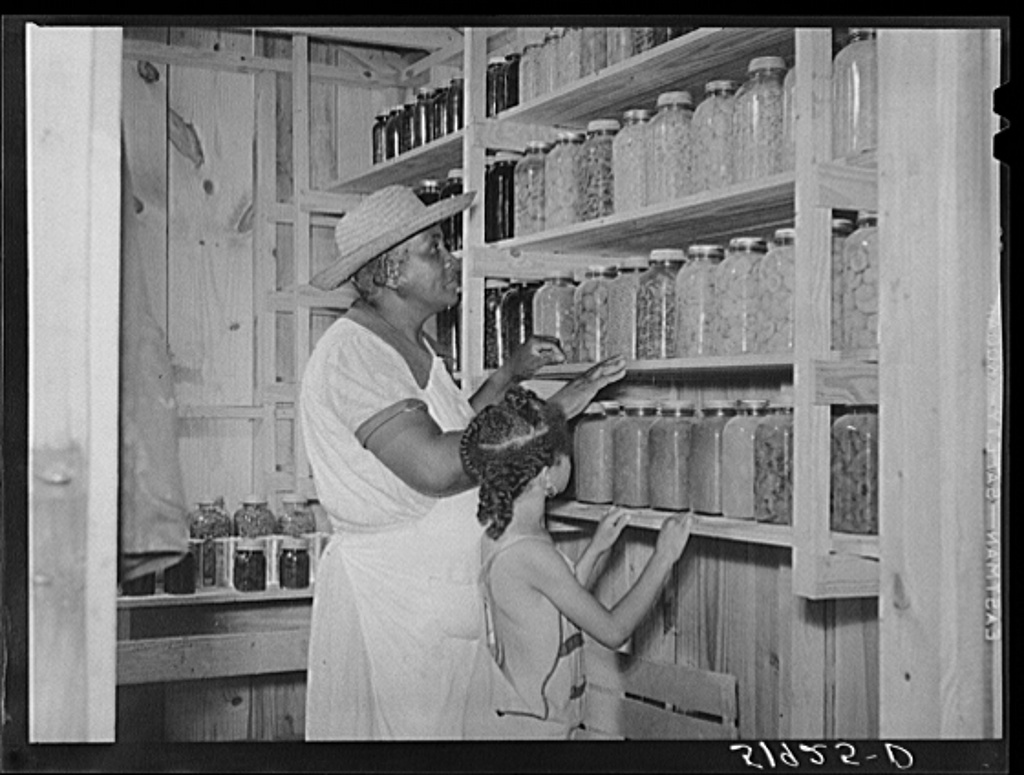 Wife of Frederick Oliver, tenant purchase client, with her canned goods in smokehouse. Summerton, South Carolina