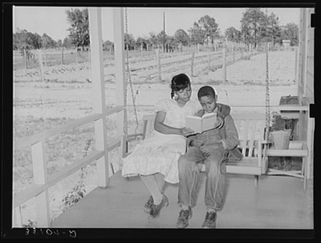 Wife of FSA (Farm Security Administration) client reading book to her son on swing on her front porch. Notice garden in background and title of book. Sabine Farms, Marshall, Texas