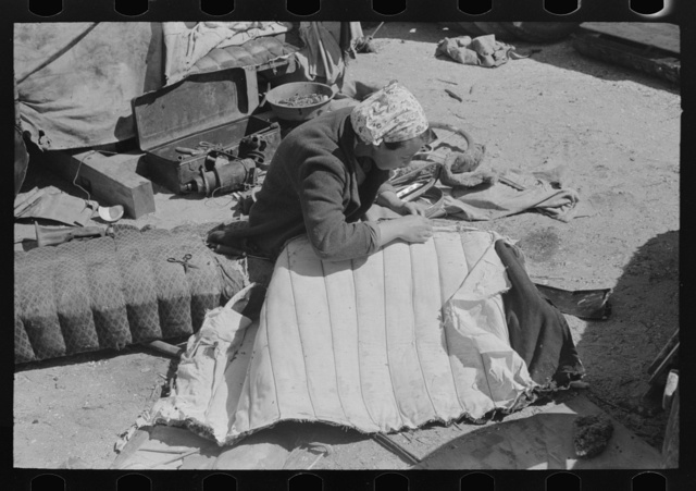 Wife of migrant auto wrecker sewing seat cushion of wrecked auto, Corpus Christi, Texas