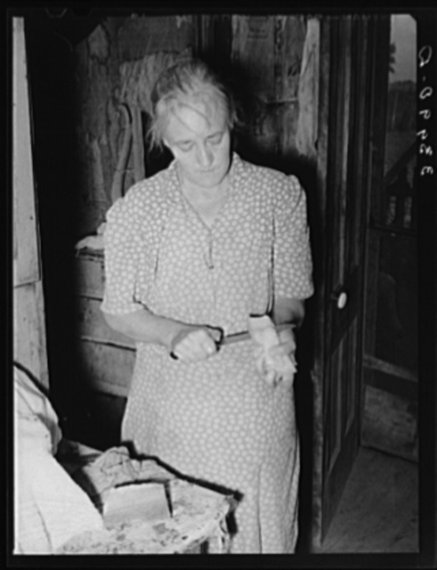 Wife of tenant farmer slicing fatback for noonday meal near Muskogee, Oklahoma. See general caption 20