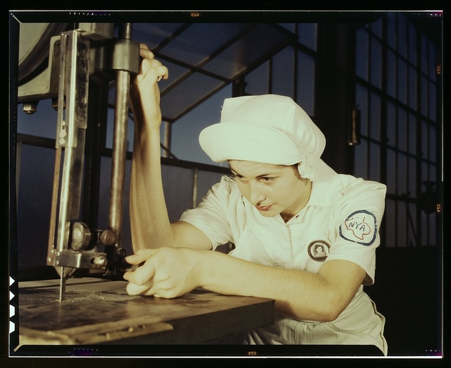 """Women in white"" doctor Navy planes (motors) at the Naval Air Base, Corpus Christi, Texas. Mildred Webb, an NYA trainee at the base, is learning to operate a cutting machine in the Assembly and Repair Department. After about eight weeks as an apprentice she will be eligible for a civil service job in the capacity for which she has been trained"
