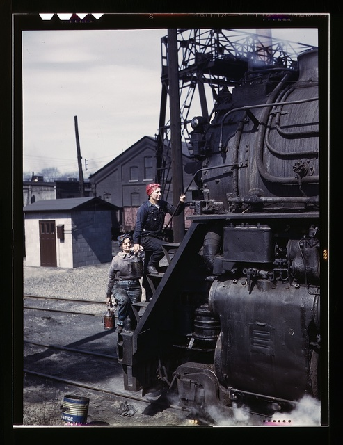 """Women wipers of the Chicago and North Western Railroad cleaning one of the giant """"H"""" class locomotives, Clinton, Iowa. Mrs. Marcella Hart and Mrs. Viola Sievers"""