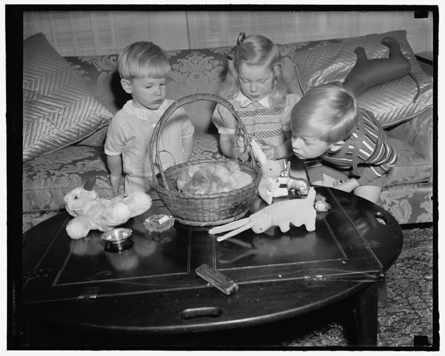 Woodring children get preview of their Easter Basket. Washington, D.C., April 5. The Woodring children, sons and daughter of the Secretary of War and Mrs. Harry H. Woodring, were given a preview today of what to expect from the Easter Bunny on Sunday. The children, left to right: Cooper, Melissa and Marcus Coolidge are expected to roll their eggs at the White House on Easter Monday, 4/5/39