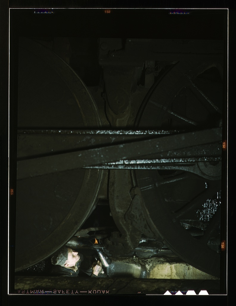 Worker inspecting a locomotive on a pit in the roundhouse at the C & NW RR's Proviso yard, Chicago, Ill.