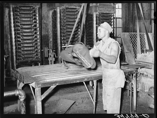 Workman removing cotton seed cake from mat after oil has been removed. The cake is removed by means of a mandrel machine. Cotton seed oil mill, McLennan County, Texas. The movement of this machine was so fast that it was impossible to stop the action with fastest shutter speed of the camera