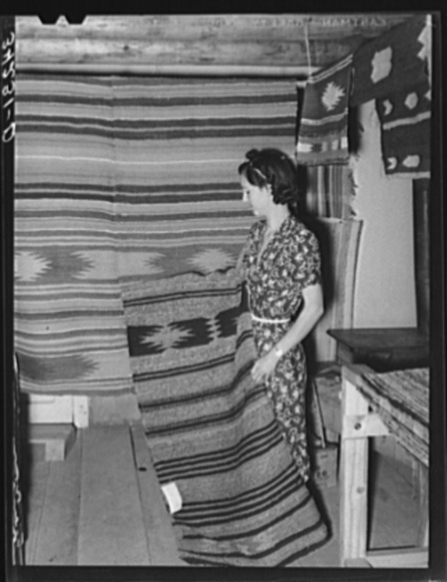 WPA (Works Progress Administartion/Work Projects Administration) project supervisor displaying some of the articles made at her weaving project. Costilla, New Mexico