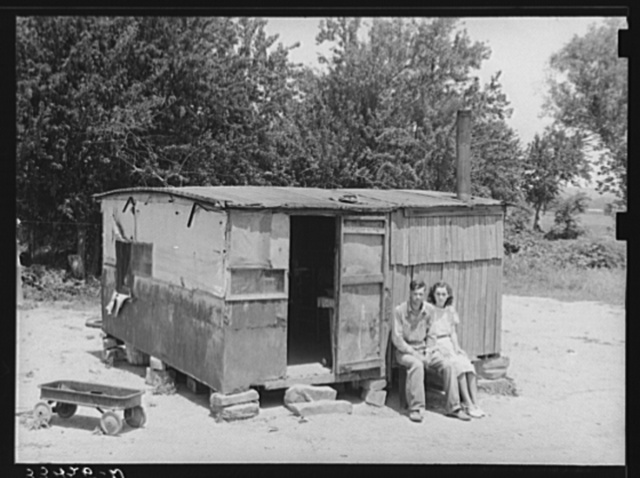 "WPA (Works Progress/Work Projects Administration) worker and his wife sitting in front of their shack home on the Arkansas River near Webbers Falls, Oklahoma. This man said that last year he thought maybe he would be a little better off when he got the WPA work and had a small amount of cash coming in but that he was worse off now. ""Last year I had a cow and some chickens and I had to sell my cow and eat my chickens. I get worse off every year"""
