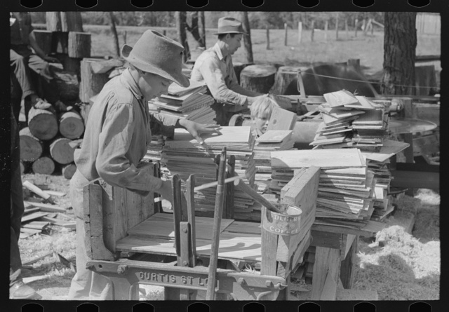 Young boy packing shingles at small mill near Jefferson, Texas