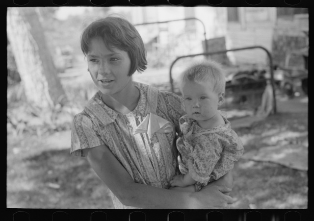 Young girl holding baby brother in her arms, community camp, Oklahoma City Oklahoma