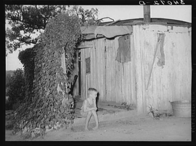 Young son of unemployed oil worker sitting on front porch of home. Seminole, Oklahoma