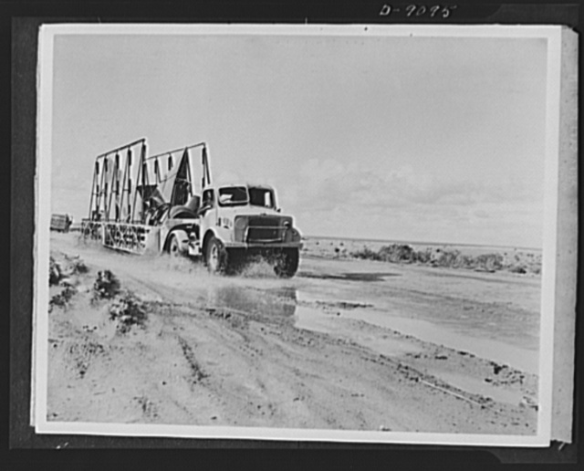 8th Army in Tripoli. A Royal Air Force salvage unit plows through mud and water carrying replacement parts which will return a damaged plane to action in the Tripoli campaign