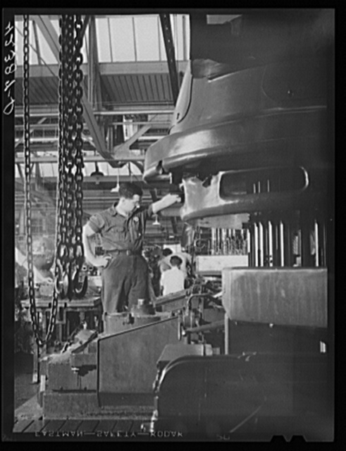 A special drill press cuts a great number of holes simultaneously in casings for engines at the Pratt and Whitney Aircraft Corporation. East Hartford, Connecticut