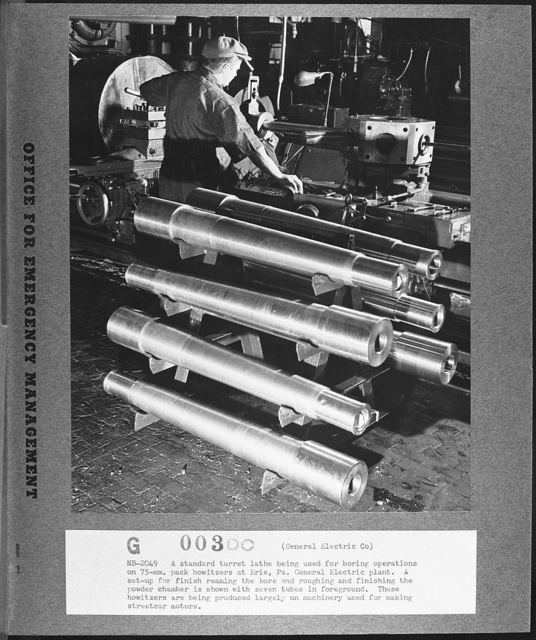 A standard turret lathe being used for boring operations on seventy-five millimeter pack howitzers at the Erie, Pennsylvania, General Electric plant.  A set-up for finish reaming the bore and roughing and finishing the powder chamber is shown with seven tubes in the foreground. These howitzers are being produced largely on machinery formerly used for making streetcar motors