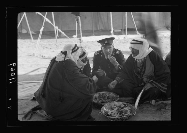 A tribal lunch at cavalry post at Tel-el-Meleiha, 20 miles North of Beersheba, Jan. 18, 1940. A group of Sheikhs & Inspector Stevens dining together