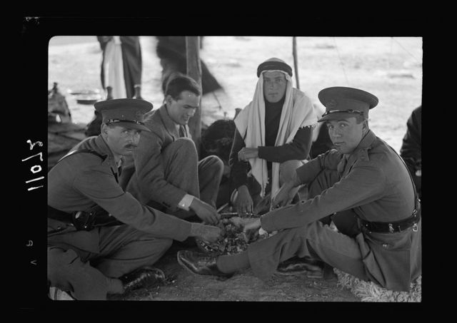 A tribal lunch at cavalry post at Tel-el-Meleiha, 20 miles North of Beersheba, Jan. 18, 1940. Holme, Bell & military offices dining in Oriental style, close up