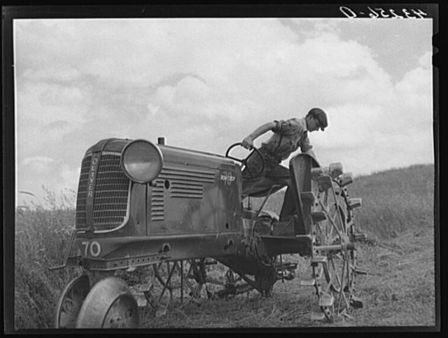 Adjusting mower on farm near Rockville, Maryland