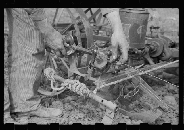 Adjusting wire on corn planter, Monona County, Iowa