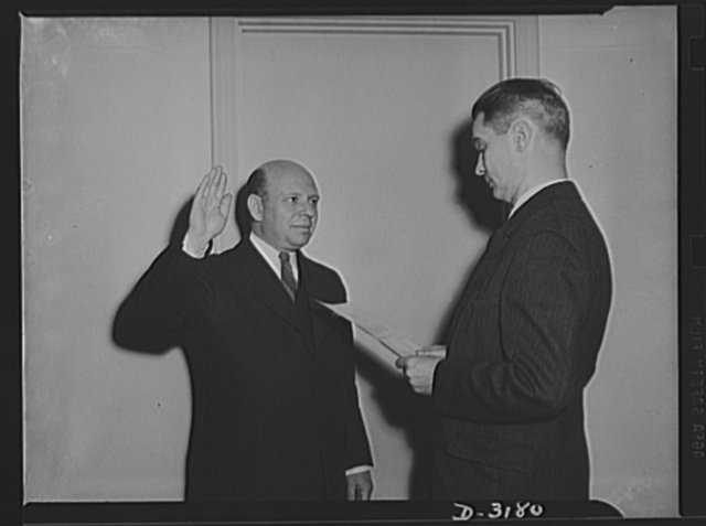 Administering oath. Herbert Emmerich, former Secretary of War Production Board, now Administrator of Defense housing Authority and J.C. Hale, of Bureau of Budget, Assistant Administrator Officer, administering the oath