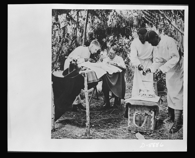 Advanced dressing station in West Africa. An operation is performed in a camouflaged operating station while native Africans in the medical unit assist the medical officers. Africans in this group include nursing orderlies, stretcher bearers, ambulance drivers, enlisted personnel and mess servants. The majority come from the coastal and central (Ashanti) districts