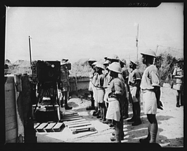 African natives prepare for air attack. Guarding against possible enemy attacks in Africa, crack veterans of the Battle of Britain are instructing African natives in anti-aircraft units. New African recruits listen attentively as the instructor, a British artilleryman, explains the operation of a radio range finder