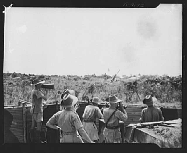 "African natives prepare for air attack. Guarding against possible enemy attacks in Africa, crack veterans of the Battle of Britain are instructing African natives in anti-aircraft units. In the foreground, officers in the command post keep their eyes on the target as the gun immediately ahead of them fires. The command post is referred to as the ""Brain Trust"" by the gunners"