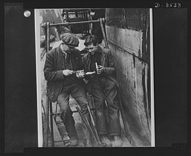 American food for British workers. Ship repairers at the Surrey Docks open a tin of American meat to make sandwiches for their lunch