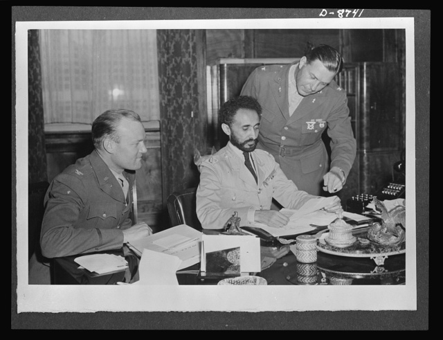 American military delegation calling on Haile Selassie. Poring over official papers. At the left of His Majesty, Haile Selassie, Emperor of Ethiopia, is Colonel Bishop, while at the right, standing, is Colonel Clark. These pictures are the first to be taken for publication since His Majesty's return to become a fighting member of the United Nations