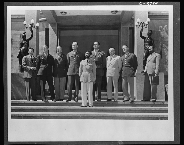 American military delegation calling on Haile Sellassie. At the conclusion of the conference, His Majesty, Haile Sellassie, Emperor of Ethiopia, posed on the palace steps with the entire American delegation. They are, left to right: F. N. Polangin, Captain Conrad, Lieutenant Colonel Baughey, Colonels Bishop and Clark, George Strompl, Captain Powers, and Tafarra Worq. These pictures are the first to be taken for publication since His Majesty's return to become a fighting member of the United Nations