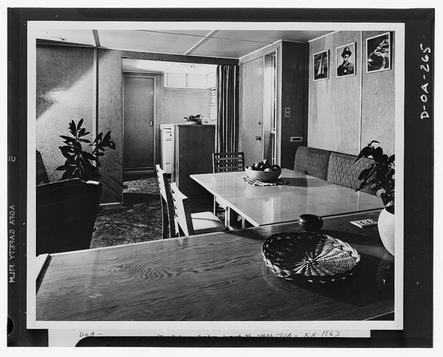 An interior of the Tennessee Valley Authority (TVA) experimental trailer-house, looking through the living-dining room into the kitchen. Walls, ceilings and floors are plywood, and the floor coverings are linoleum. Of the numerous built-in items of furniture and equipment in the house, the picture shows built-in seat, built-in kitchen stove,