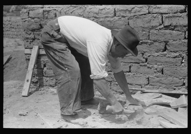 An ordinary hatchet is used to chip adobe bricks used in house construction, Penasco, New Mexico