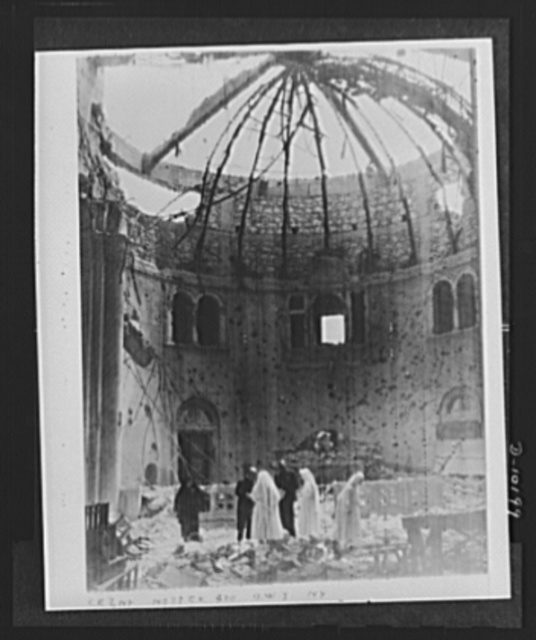 Archbishop Spellman of New York and Brigadier General Auby C. Strickland, U.S. Army 9th Air Forces, view ruins of Chapel of Franciscan Missionaries in Tripoli recently damaged by German night bombers. Monsignor Spellman was guest of General Strickland during his visit to Tripoli
