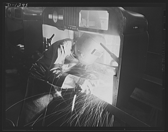 Army truck manufacture (Dodge). A veritable cascade of sparks fly when the arc welder fuses together toe risers in the front section of a Dodge army truck cab assembly