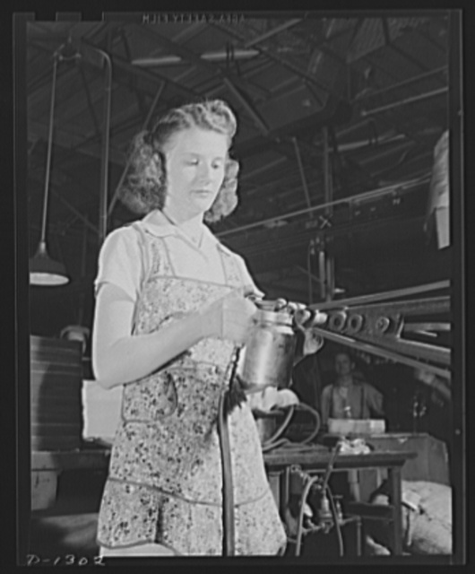 """Army truck manufacture (Dodge). An attractive young lady operating an ingenious machine contributes her share to defense production. With a specially designed """"gun"""" this girl sprays cement inside a """"U"""" shaped rubber channel into which the glass for the rear window of truck cabs is inserted. The rubber channel makes the window water-tight"""