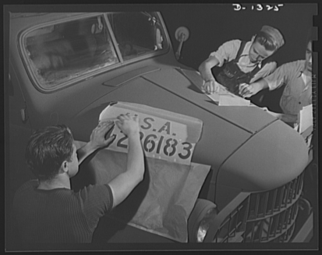 Army truck manufacture (Dodge). Close-up showing men putting stencils in place on the hood of a Dodge Army truck