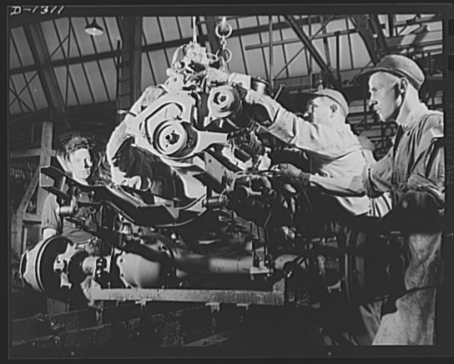 Army truck manufacture (Dodge). Dropping the power plant of a Dodge Army truck to its place in the chassis assembly. The complete motor, carried on an overhead conveyor, reaches the chassis moving along the assembly line at precisely the right time and place to permit steady production of these urgently needed army vehicles