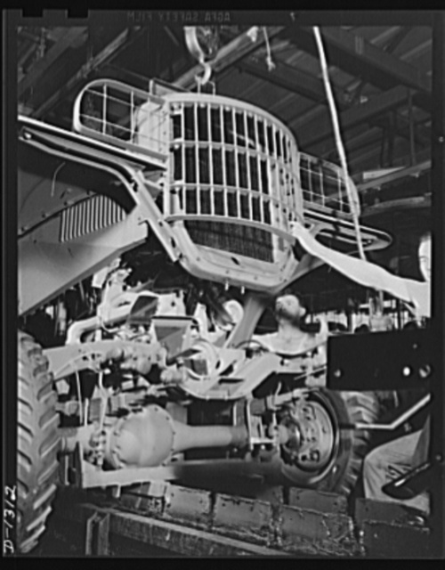 Army truck manufacture (Dodge). The radiator, brush guard, and front fender assembly of a Dodge Army truck being lowered into position as the chassis moves steadily along the assembly line