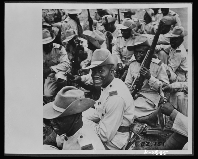 Ashanti troops in Gold Coast Regiment. Smartness in the parade ground and cheerfulness under all conditions are traditional characteristics of the Royal West African Frontier Force. Ashanti troops serving in the Gold Coast Regiment are shown resting by roadside during a break in the march